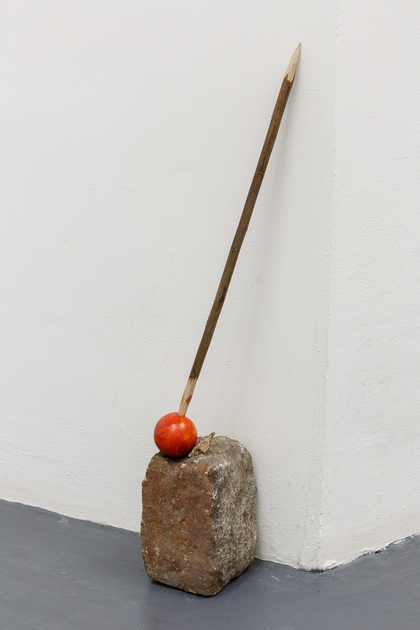 King Harold Kurios Oranj — Granite block, Whittled willow pole, blood orange, 2019.